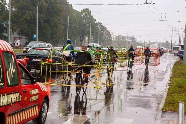 Görselde otobiller tarafından bir anlamda işgal edilen kentlerin bu durumunu protestol etmek için bisikletlerin üzerine ilave parçalar ekleyerek  yolda bir otomobil kbüyüklüğünde ebatlara getirip bisiklet süren protestocular yer almakta.