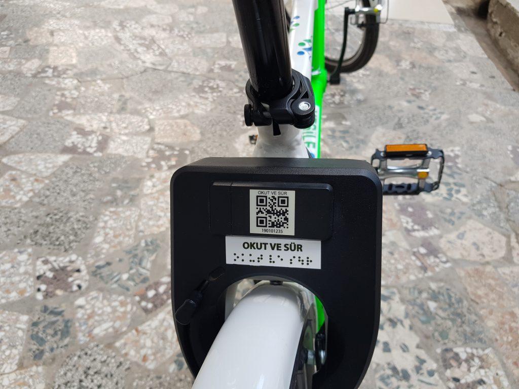 Görselde Yeşile çevir bisikletierinin arka teker üstünde yer alan kilit sistemi ve üstündeki Okut ve sür yazısı yer almak
