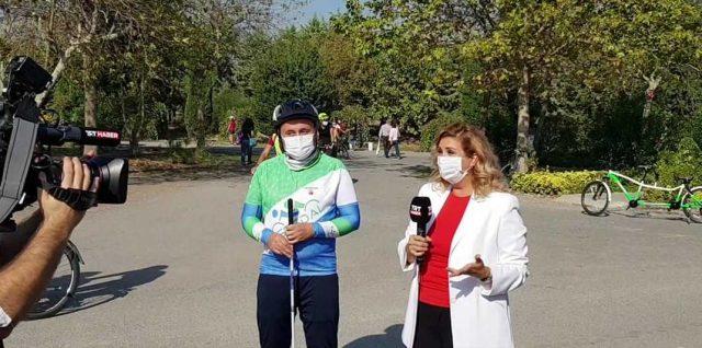 Dernek başkanı Fatih Söylemez TRT spikeri ile röportaj halinde. Arka fonda ağaçlar ve bir tandem .Solda kameraman görünmekte